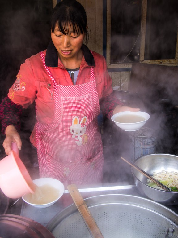woman cooking noodles on the street in china