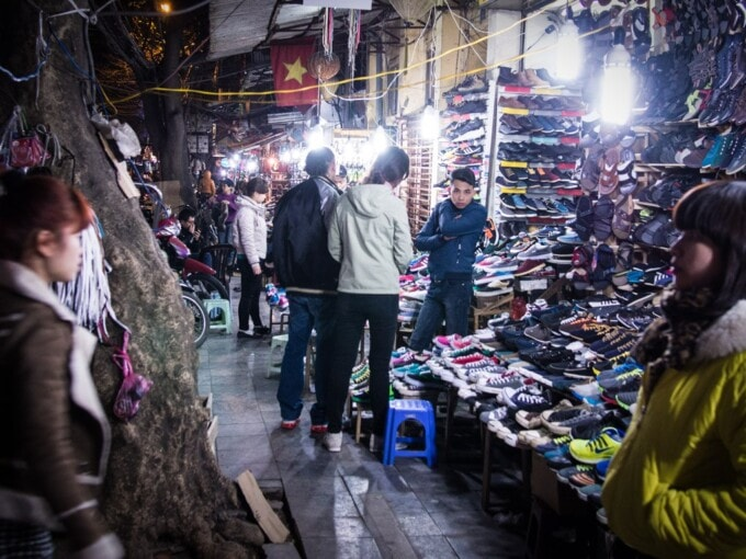 couple looks at piles of shoes in hanoi