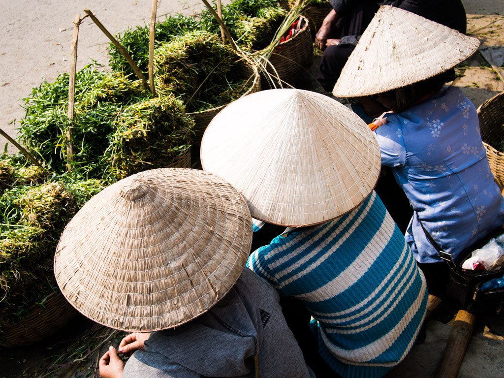 three women wear pointed hats in tuan giao