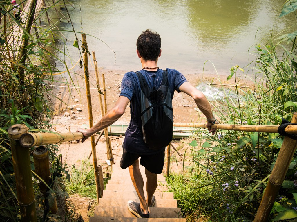 stephen walking down bamboo stairs in laos