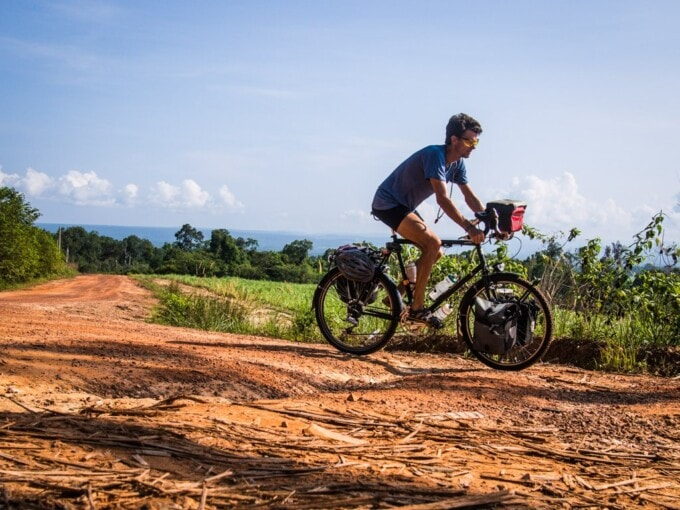 cyclist on a red dirt road cambodia