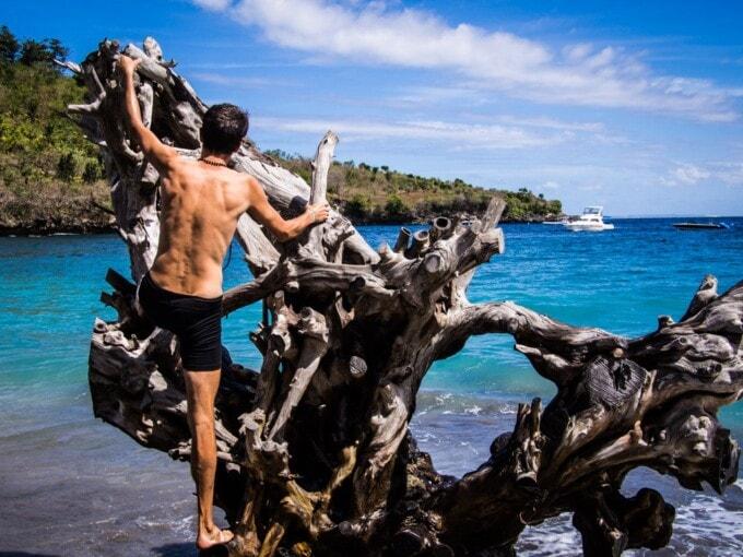 man climbing a tree root in crystal bay nusa penida