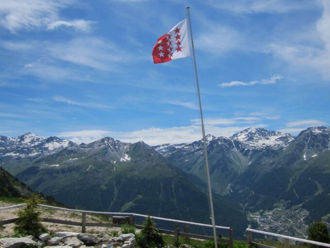 swiss flag in front of an expanse of mountain peaks