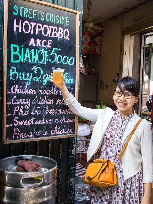 female tour guide with cup of fresh beer in hanoi