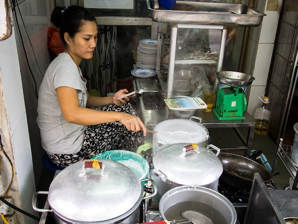 woman cooking noodles at a street food stall