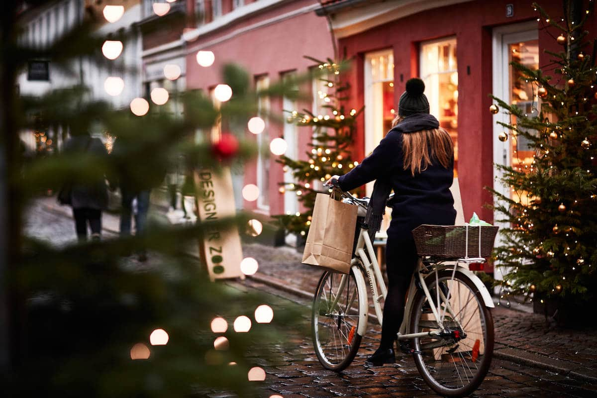 woman pushing bicycle past christmas trees in aarhus denmark