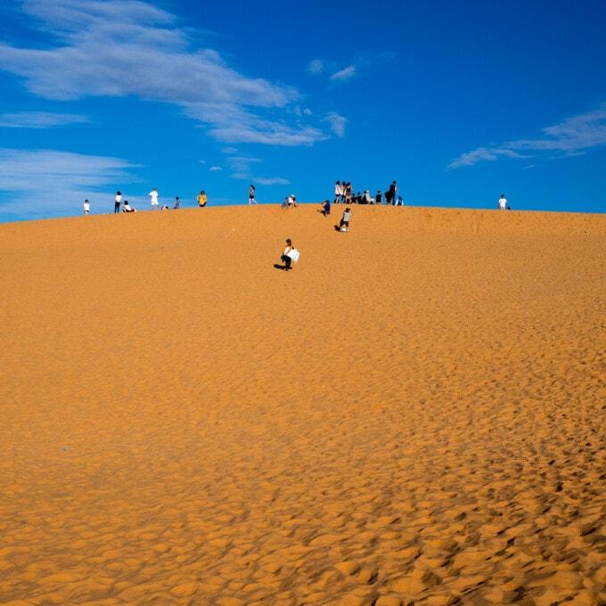 families climbing the red sand dunes mui ne
