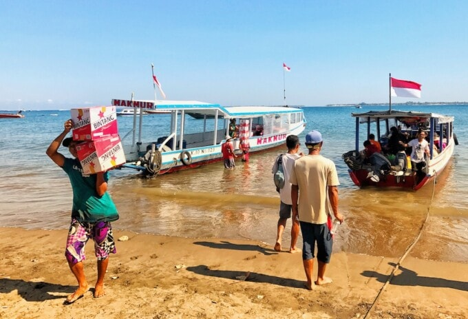 man carrying boxes of bintang beer from wooden boats in the water on the gili islands