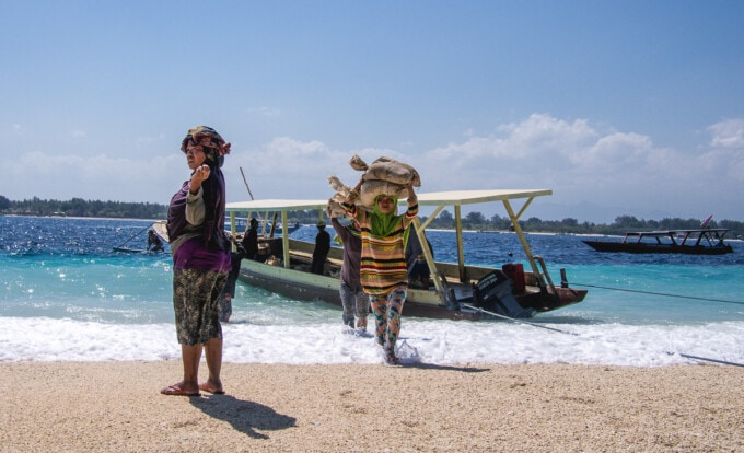 women carrying bags of goods balanced on their heads from a boat