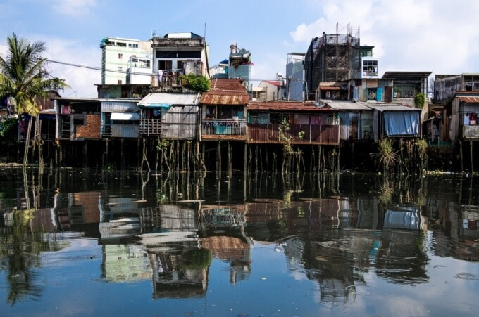 stilt shacks reflected in the mekong river water