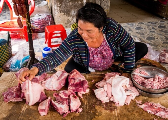 a woman handles meat on display at a vietnamese market