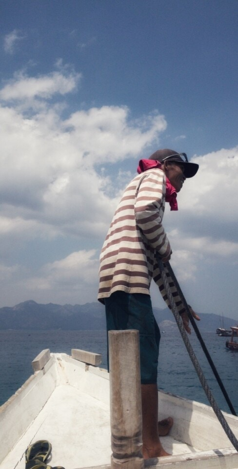 indonesian man in a striped shirt pulling in a line on a wooden boat