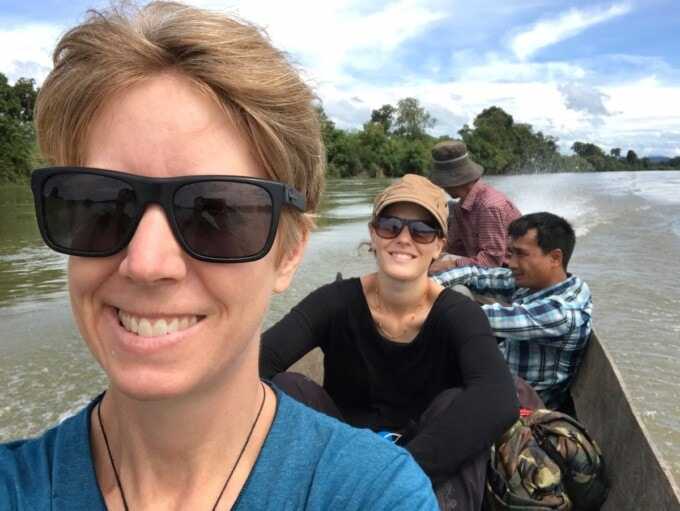 tourists in cambodian wooden longboat