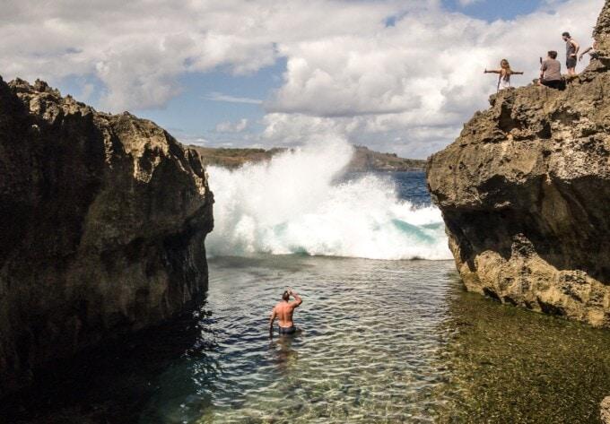 man swimming in angel's billabong with huge waves crashing