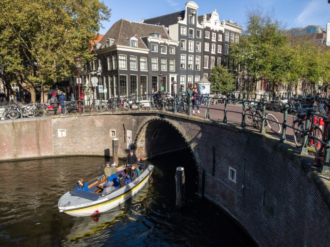 boat going under a bridge in amsterdam