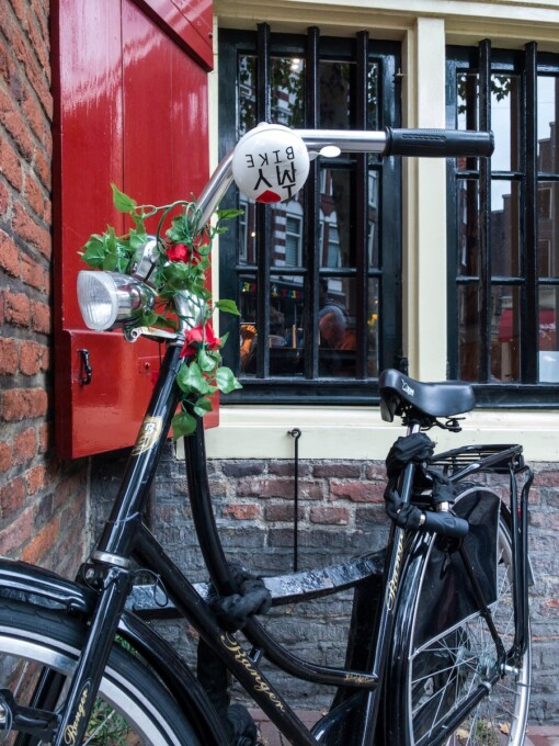 black bicycle in front of red shutters in amsterdam