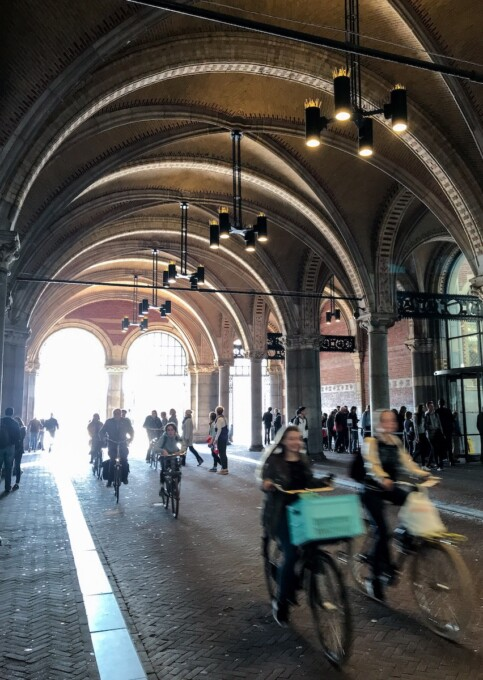 cyclists riding by the rijksmuseum in amsterdam