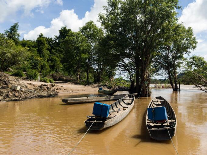 wooden longboats in murky flood water 4000 islands laos