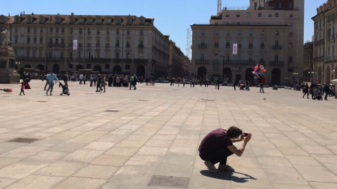 man crouching to take a picture piazza castello torino