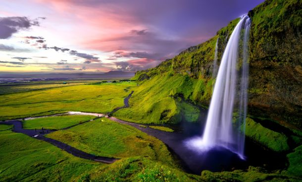 waterfall in iceland on green landscape