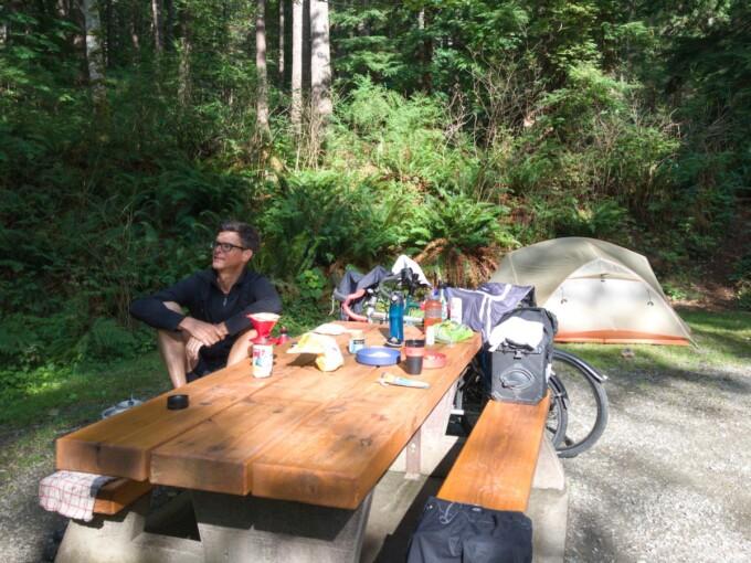 man at a picnic table and tent