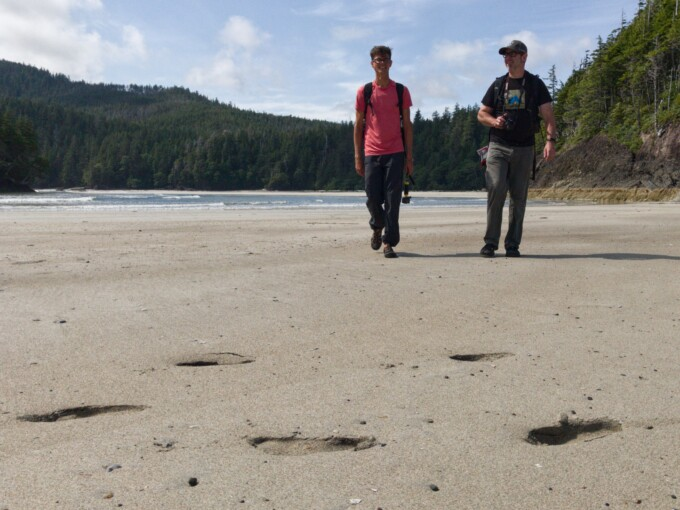 two men walking on a beach