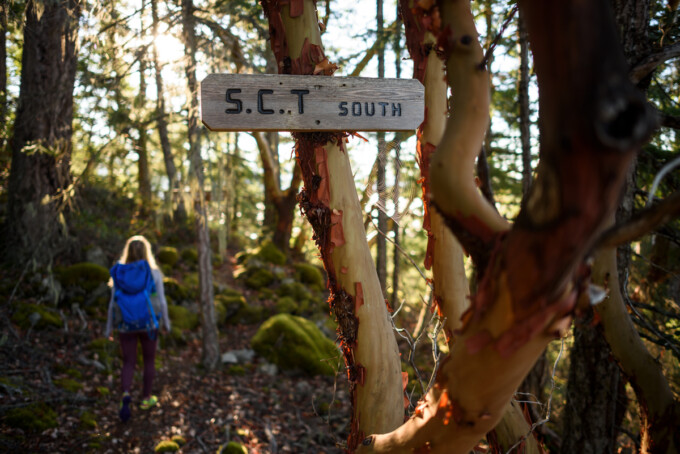 woman hiking in the woods sign says sct south
