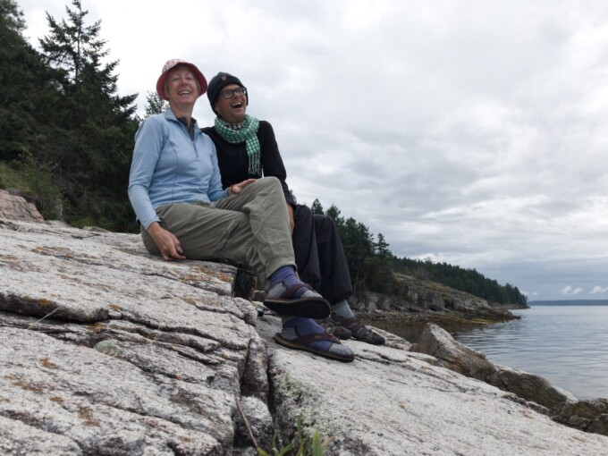 jane and stephen sitting on a rocky shoreline