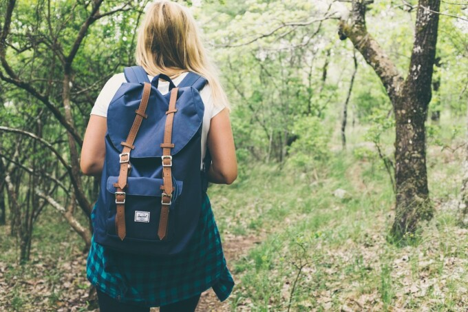 woman hiking in the woods with a backpack