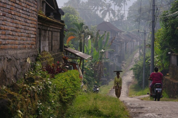 small back road in bali with women dressed in traditional clothing