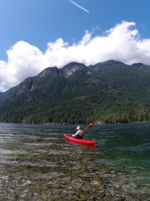 woman in a kayak under a blue sky