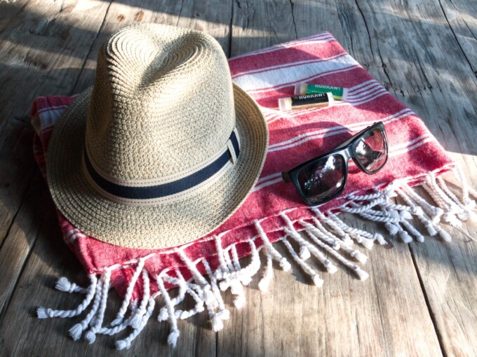 red sarong with straw sunhat and sunglasses