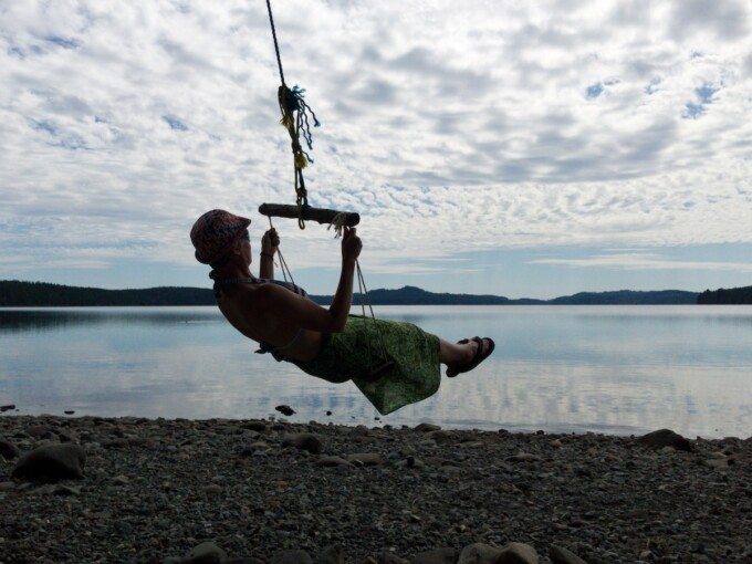 woman on a wooden swing in front of a beautiful lake