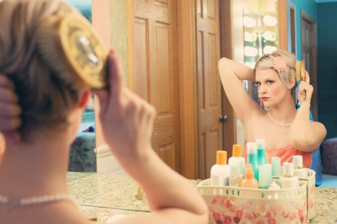 woman preening in the mirror