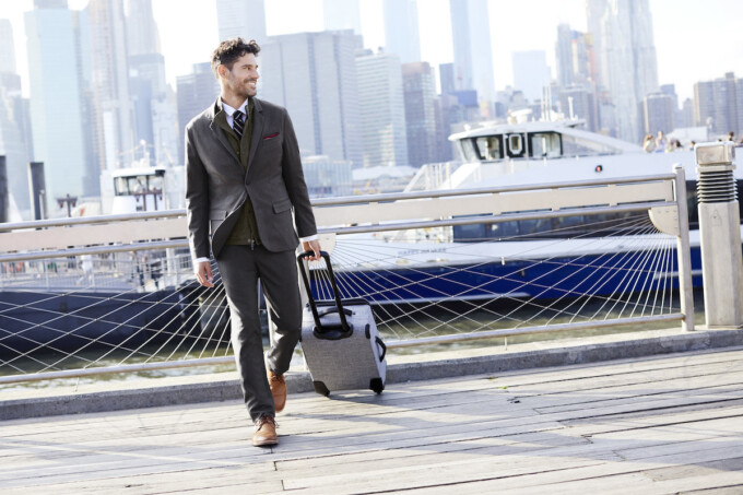 man in suit rolling suitcase behind