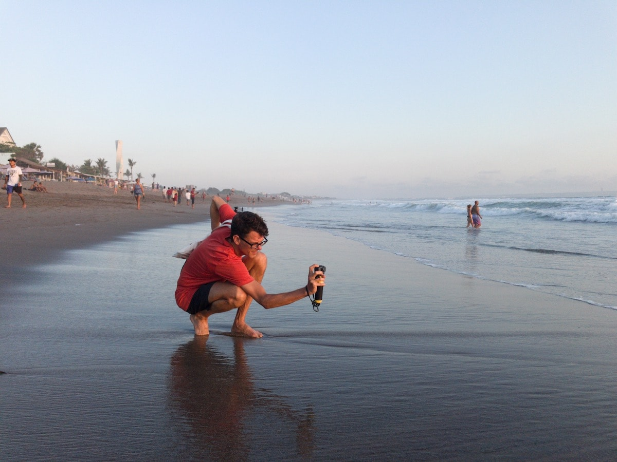 stephen crouching on beach using the osmo action camera
