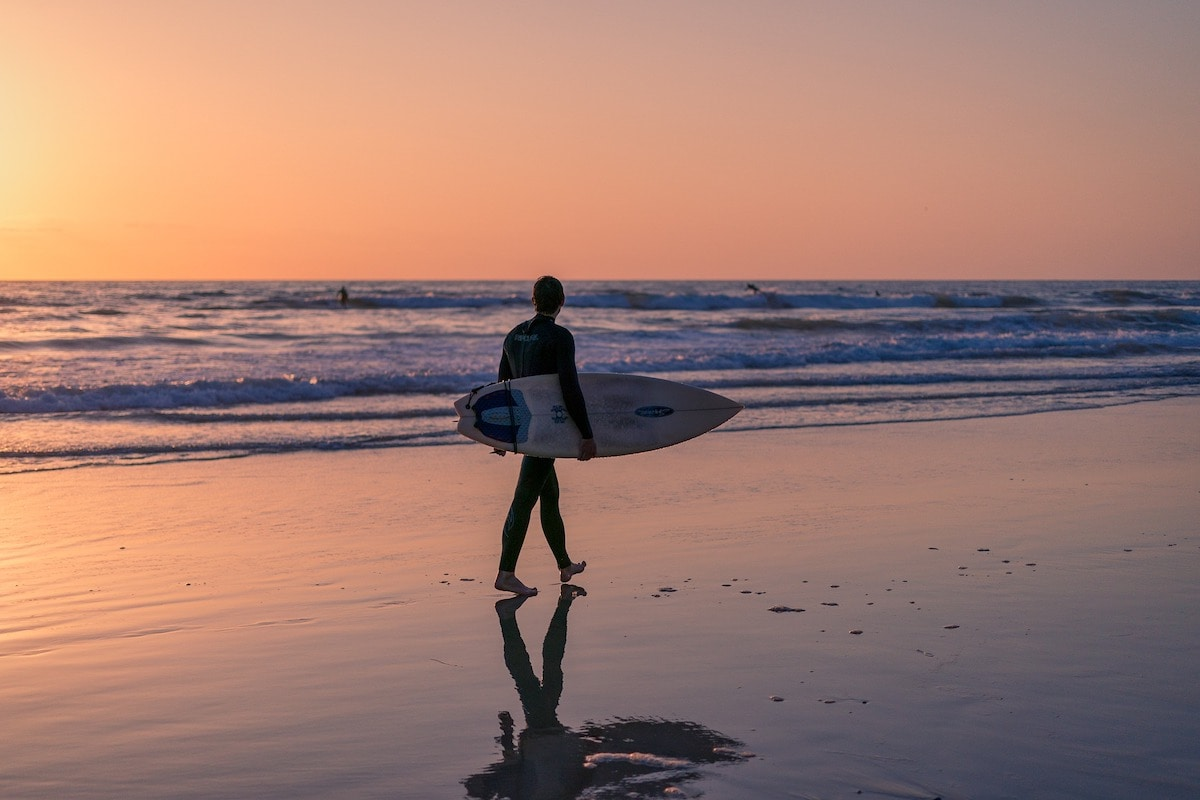 man carrying surf board on the beach at sunset