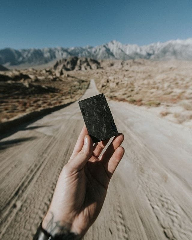 man holding travel wallet on a dusty road