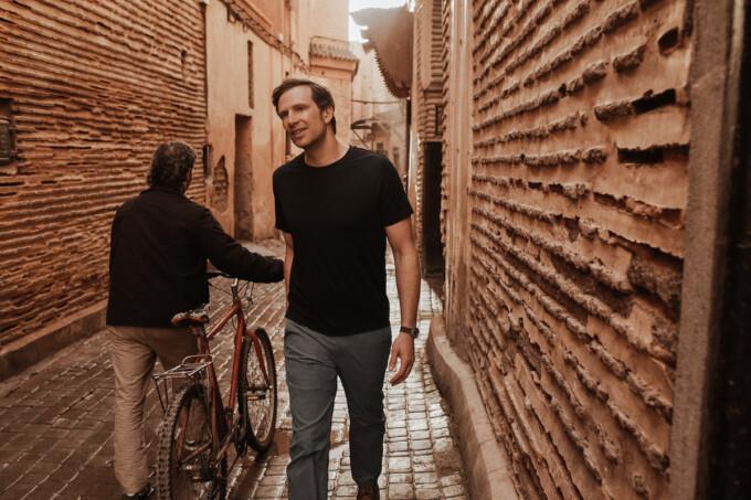 homme marchant dans une ruelle étroite, habillé de bons vêtements de voyage