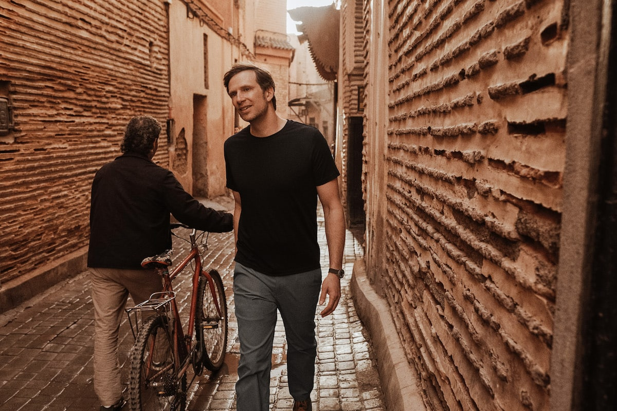 man waking down a narrow alley dressed in good travel clothes