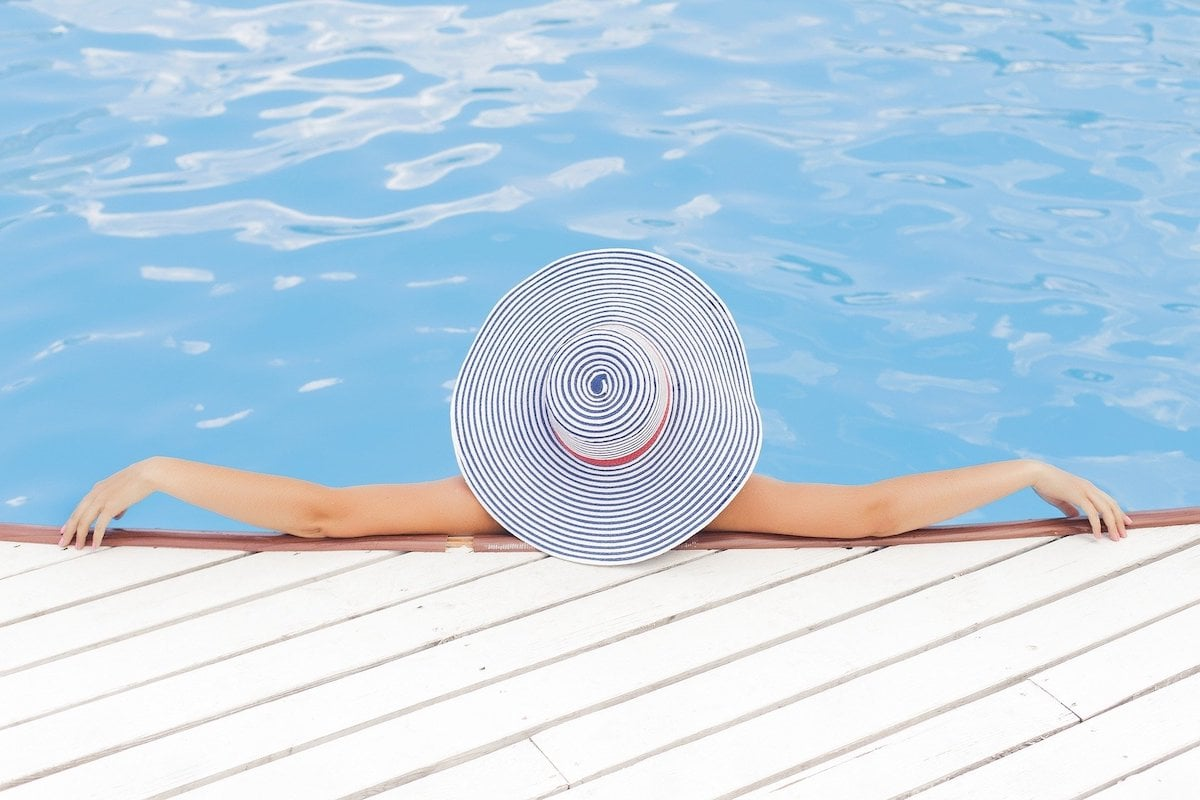 woman in a swimming pool wearing a sun hat