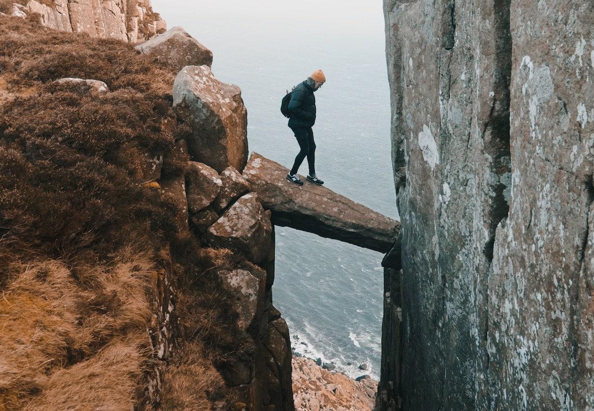 man walking across a rock bridge high above a beach