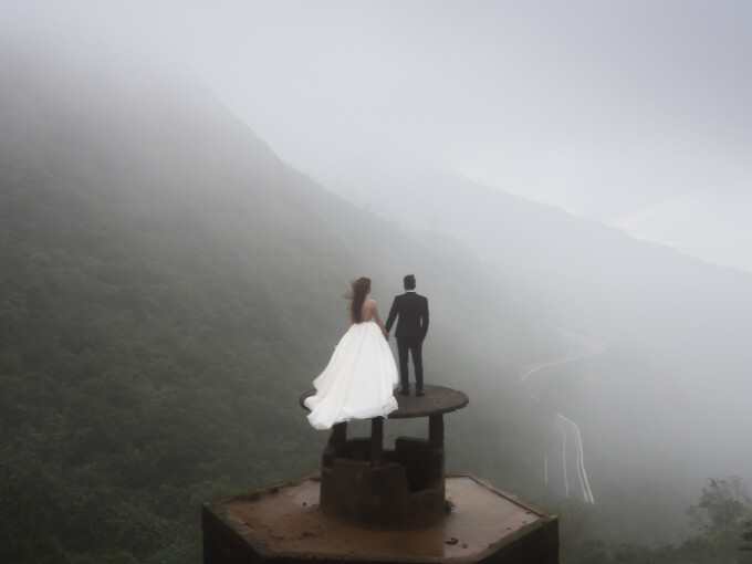 Bride and groom posing for wedding pics at the top of Hai Van Pass.