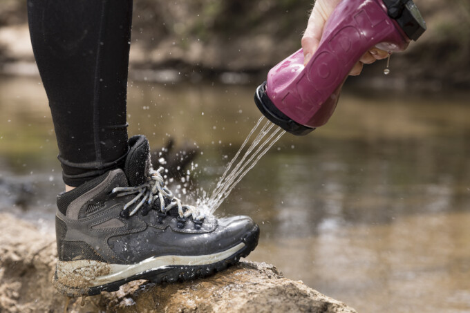 person using special bottle lid to spray mud off of hiking boots