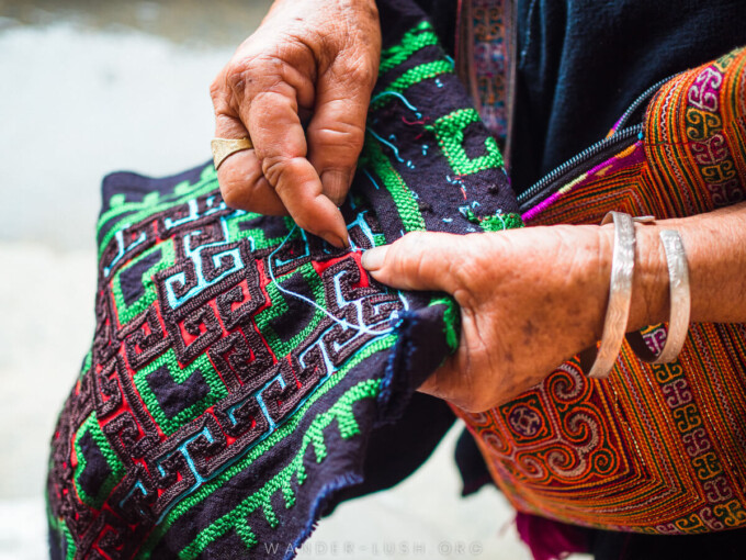 hmong woman embroidering a colorful cloth in vietnam