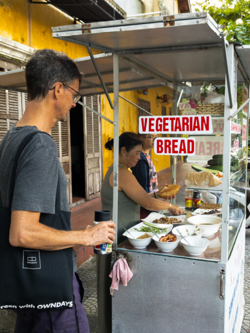 stephen waits at the vegan banh mi stall in hoi an