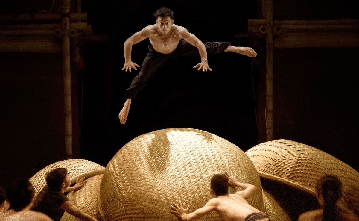 man leaping over very large baskets