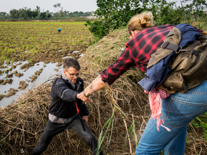 photo tour guide helping stephen through muddy field hoi an vietnam