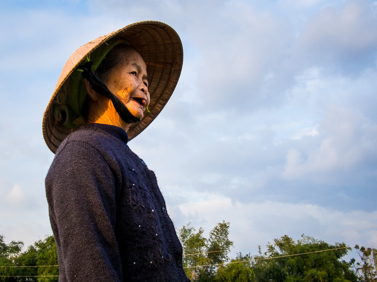 woman wearing a conical hat looking into the distance