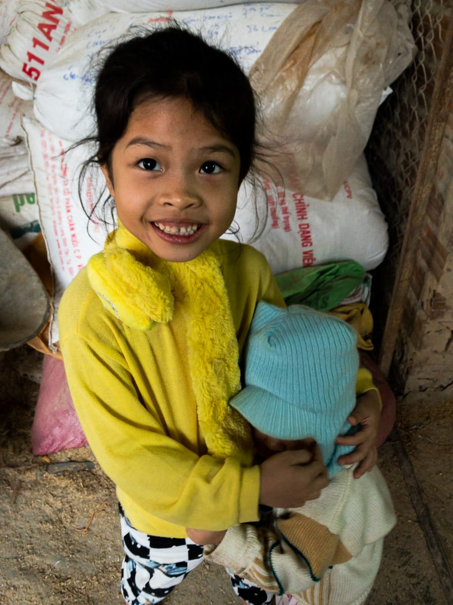 small girl in yellow smiling for the camera